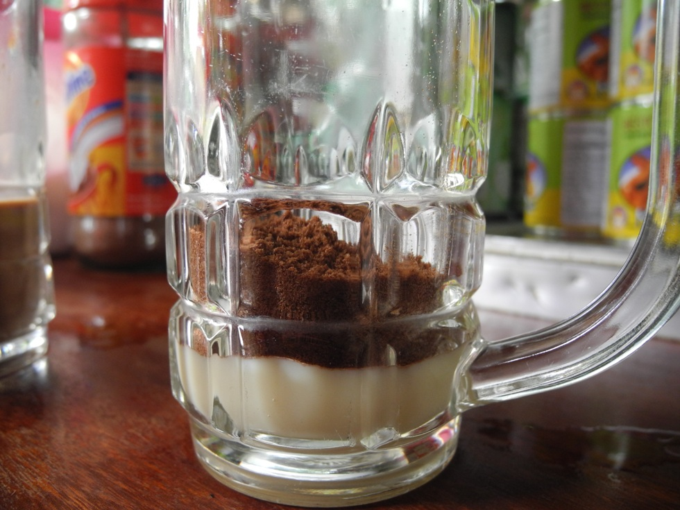 A lot of sweet condensed milk and / or sugar cane sirup with even more Ovaltine powder mixed with a dash of boiling water and served on a glass full of ice cubes. Now the only thing you have to do is to wait until the drink has the consistence that you like best: not too watery but yet not too concentrated.