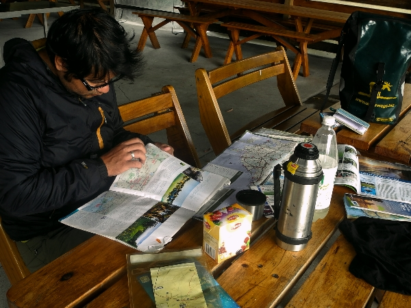 Planning the day with a hot tea and some snacks. The cooking area keeps the rain off.